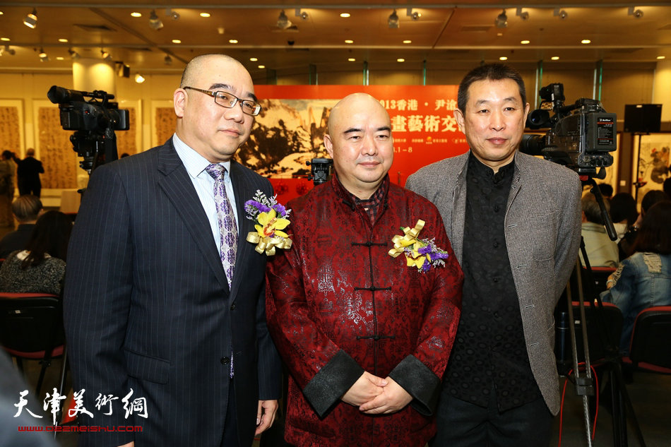 2013香港·尹沧海教授书画艺术交流展在香港中央图书馆举办。图为尹沧海教授与香港《文汇报》执行总编吴明先生及好友赵铁标先生在展览现场。