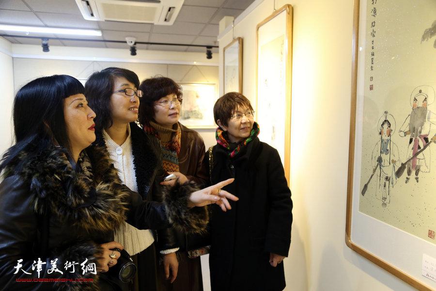 """""""美丽中国―天津市女书画家精品展""""在天津群艺馆举行,图为女画家黄雅丽讲解自已的作品。"""