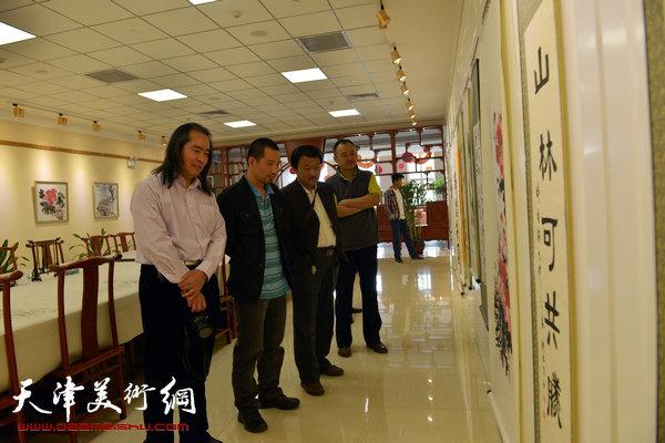 书画家在社区书画展上欣赏作品