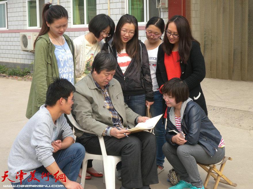天津师大陈元龙教授带领研究生到蓟县写生,图为陈老师给同学们批改作业