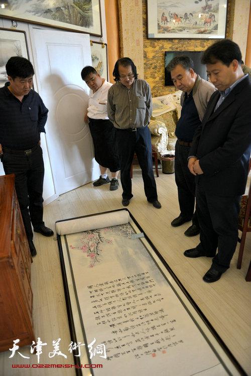 陈学周(中)与友人在观赏其作品《百鸡图》。