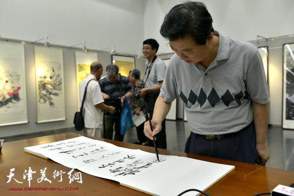 图为杨建国在画展现场。