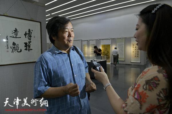 图为李建平接受媒体采访。