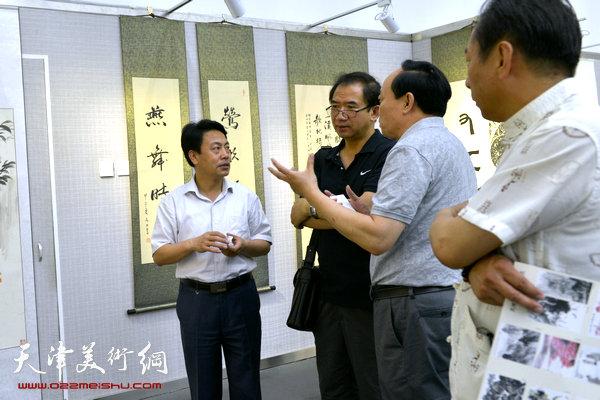图为刘俊坡、顿子斌、郑爱民在画展现场。