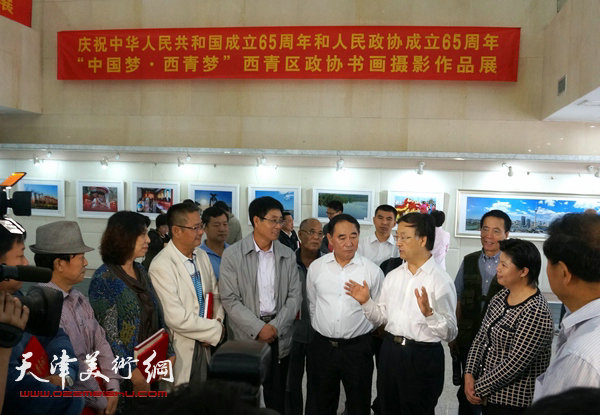 图为西青区领导在展览现场与高天武、吕爱茹等参展作者交流。