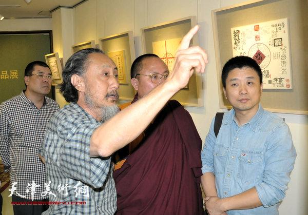 """图为刘栋在""""茶档心画—刘栋茶纸书法展""""上为来宾讲解作品。"""