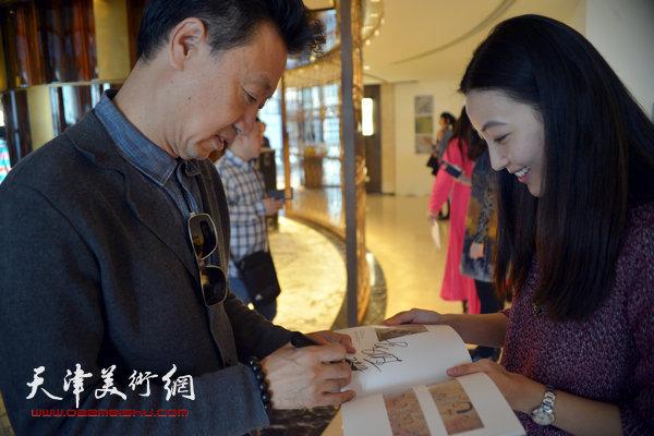 图为李旺为观众在展品册上签名。