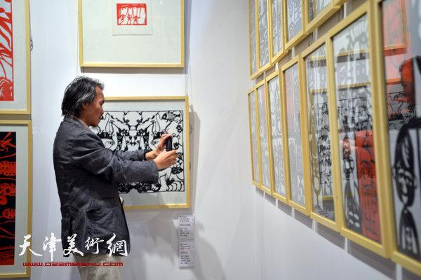 """2014""""西岸""""剪纸艺术展现场。图为天津美术学院史论系主任郭亚希。"""