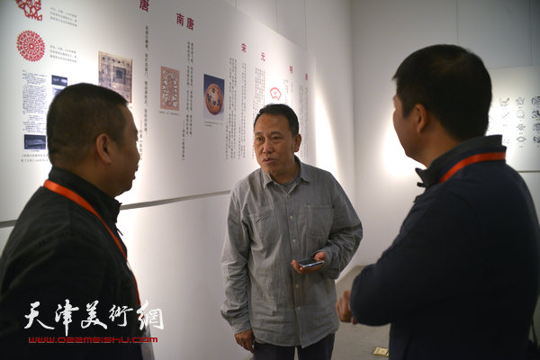 """2014""""西岸""""剪纸艺术展现场。图为天津美术学院教授阎秉会与参展作者交谈。"""