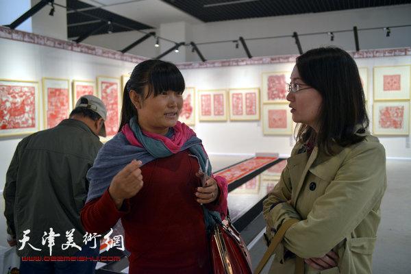 """2014""""西岸""""剪纸艺术展现场。图为北方网记者吴宏采访参展作者。"""