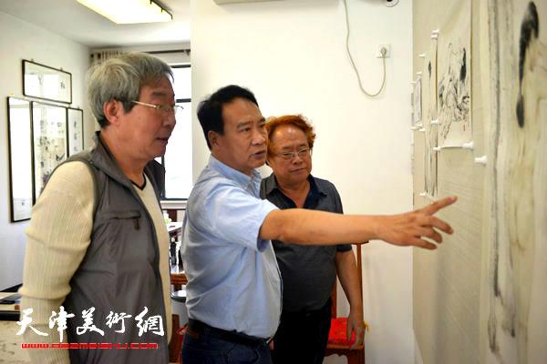 图为刘皓(右)、马寒松(中)、张亚光(左)在研究画作。