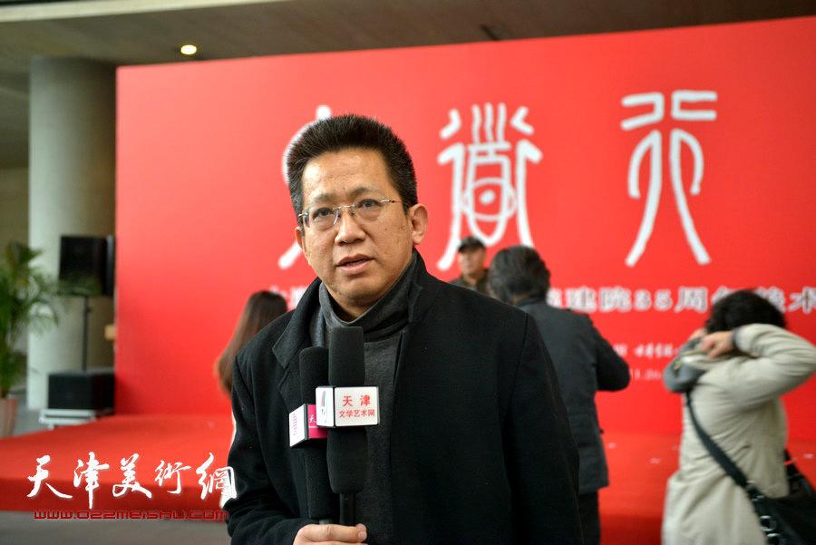 李毅峰在画展现场接受采访。