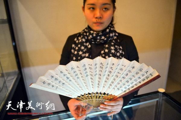 """12月12日上午,中诺国际2014秋季艺术品拍卖会预展在天津迎宾馆举行,图为工作人员展示即将上拍的""""乾隆御扇""""。"""