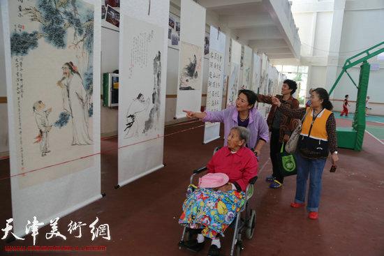 海南当地的观众推着轮椅携家眷观看画展