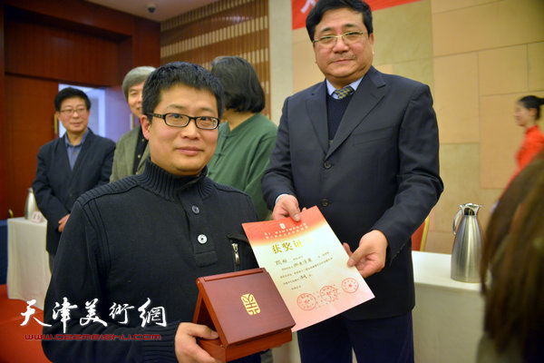 商移山为获奖的画家闫勇颁奖。