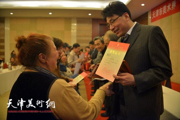 郭振山为获奖的画家魏秋明、孟繁华颁奖。
