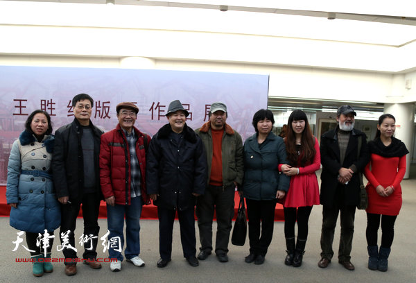 王胜红版画作品展在泰达图书馆文化展厅开幕,图为王胜红与来宾合影。