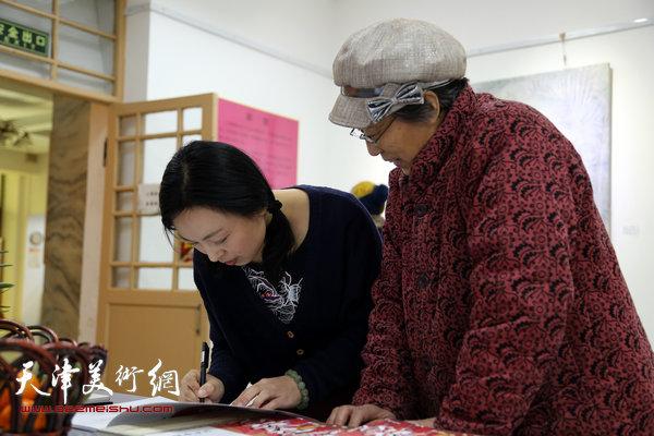 于栋华博士毕业作品展1月21日在天津大学一得轩开幕,图为于栋华为来宾在画集上签名留念。