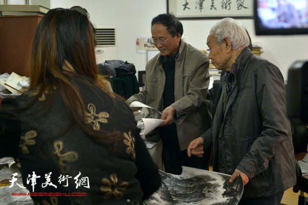 纪振民在收件现场与送展作品的画家郭金标交流