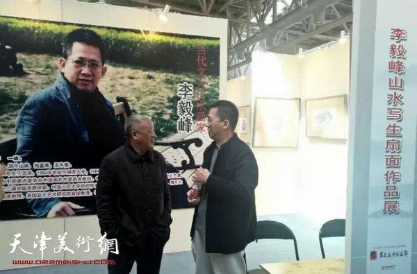 李毅峰先生(左)与著名画家何家安先生在个人作品展区进行交流