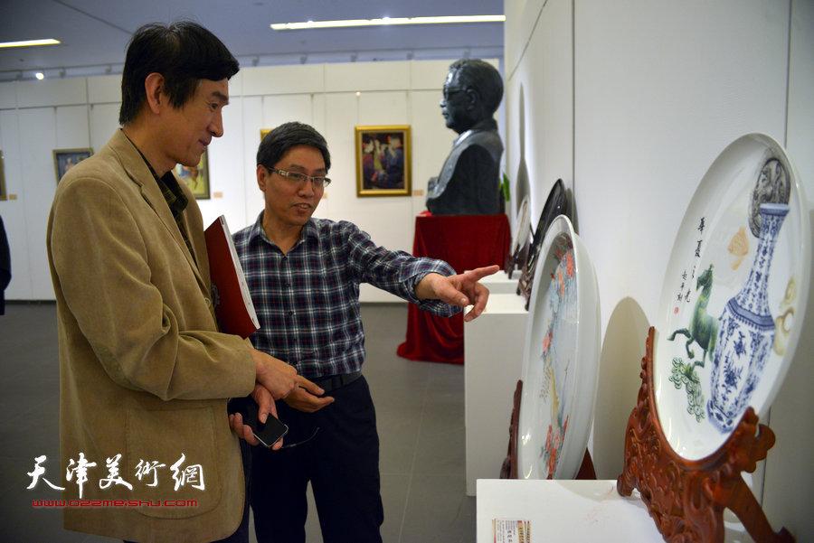 图为中国工艺美术协会秘书长王山在观赏刻瓷大师陈起平的作品。