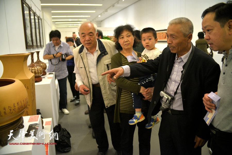 图为艺术家孙荣刚向观众介绍作品。