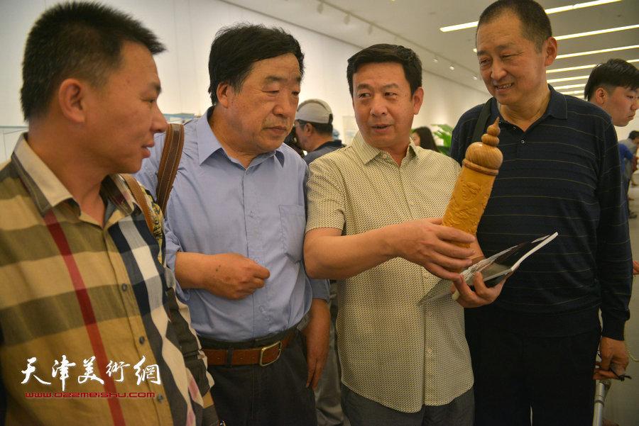 图为工艺美术大师陈大刚与刘卫东、黄金华等在展览现场。