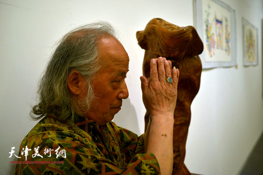 图为根雕艺术家张宗泽在展览现场。