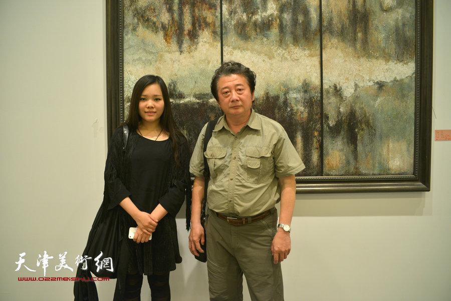 图为青年艺术家唐甜与油画家沙治国在她的木板大漆作品前。