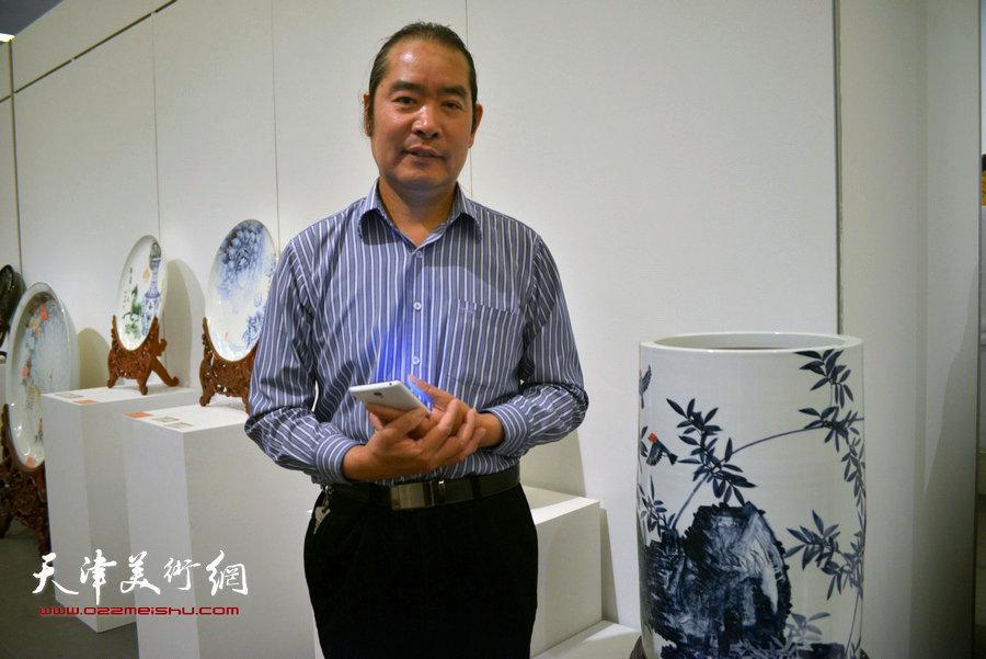 图为艺术家王东风在他的瓷艺作品前。