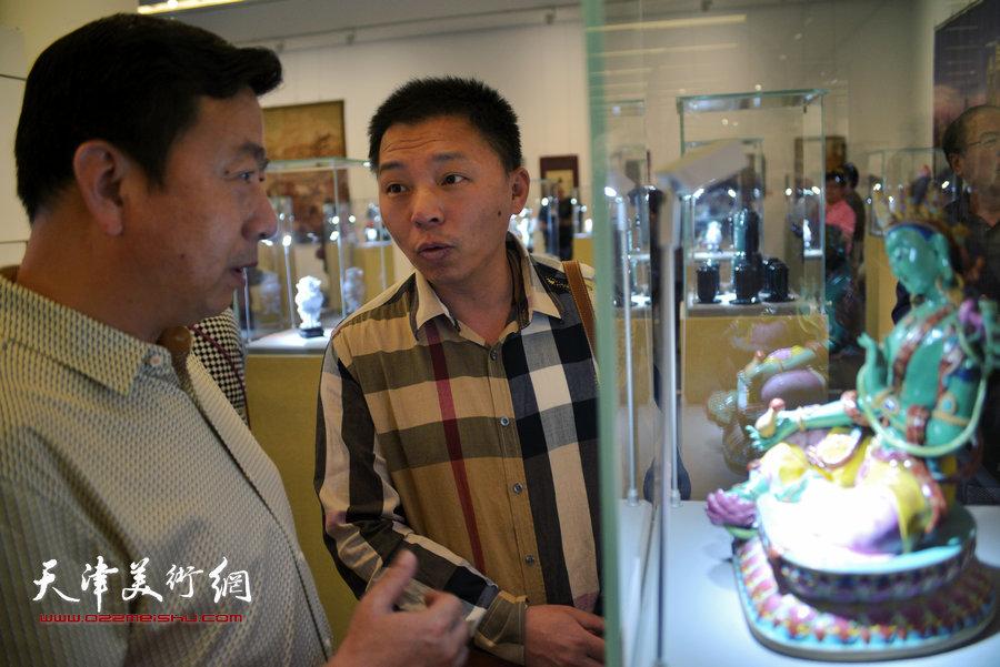 图为陈大刚、王辉在观赏陶瓷作品《菩提》。