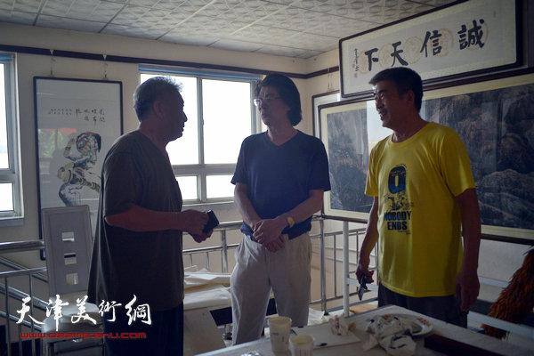图为郑连群与当地艺术家在活动现场交流。
