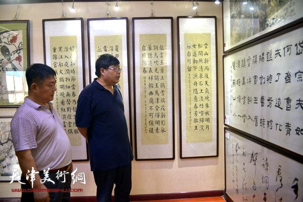 张纬东在孟庆阳的陪同下,观赏张建会的书法作品。