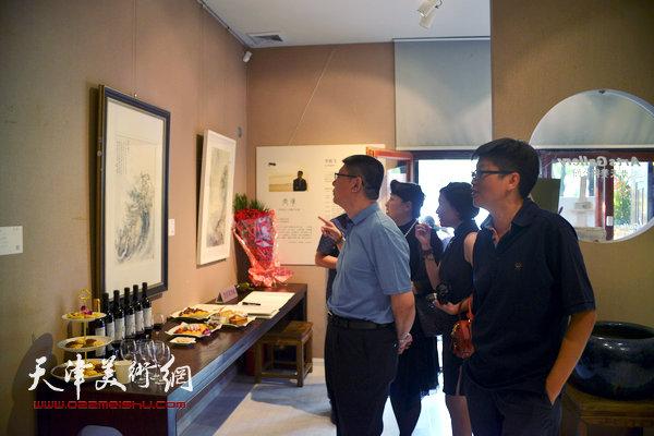 李旭飞陪同来宾观赏作品。