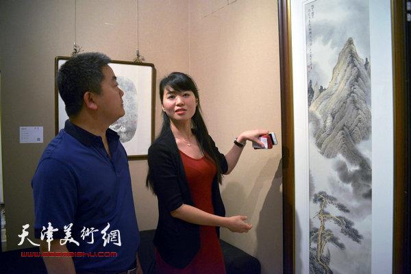 何艳萍向来宾介绍李旭飞画作。