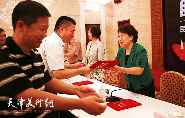 民进领导为捐赠书画作品的书画家窦宝铁、魏瑞江颁发荣誉证书。(