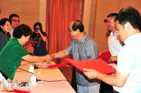 民进领导为捐赠书画作品的书画家孙占元颁发荣誉证书。(