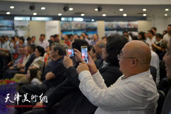 图为贾广健、尹沧海用手机拍下画展盛典。