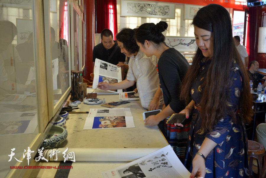 贾广健精品佳作9月13日在集真阁展出,图为贾广健为观众签名留念。