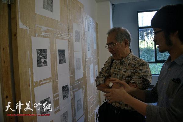 天津美术学院教授,天津藏书票研究会理事长沈延祥与滨海国际版画创作基地蒋伟在观看展品。