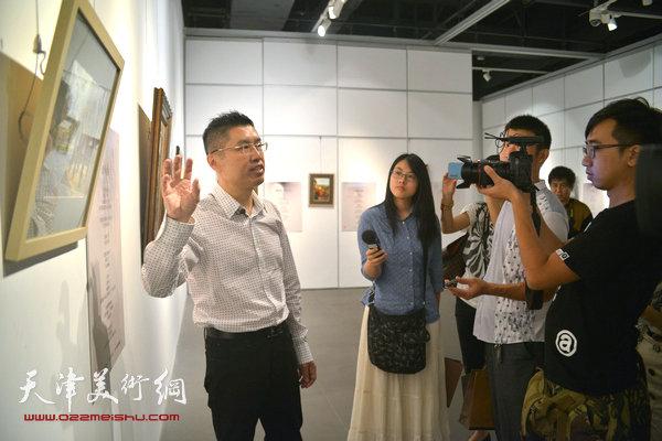 程亚杰在布展现场向记者介绍作品。
