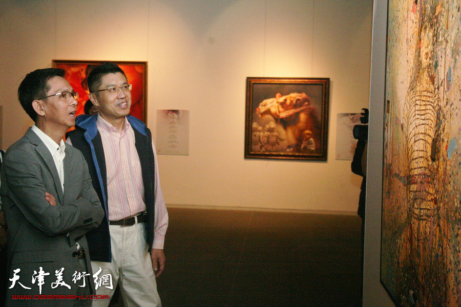 图为程亚杰与何家英在展览现场观摩画作。