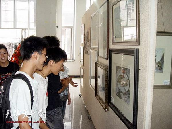 2009年6月,天津财经大学艺术学院学生观看王双成水彩作品。