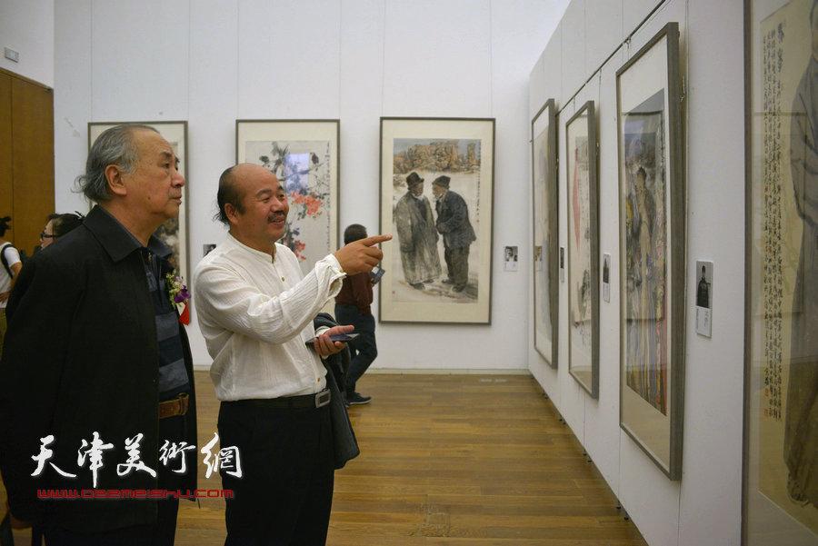 王振德、孟庆占在画展现场观赏作品。