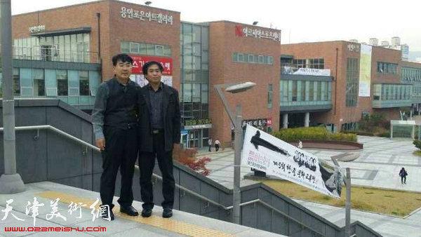 韩中文化交流振兴协会会长河太逵与天津美院教授肖培金在交流展外。