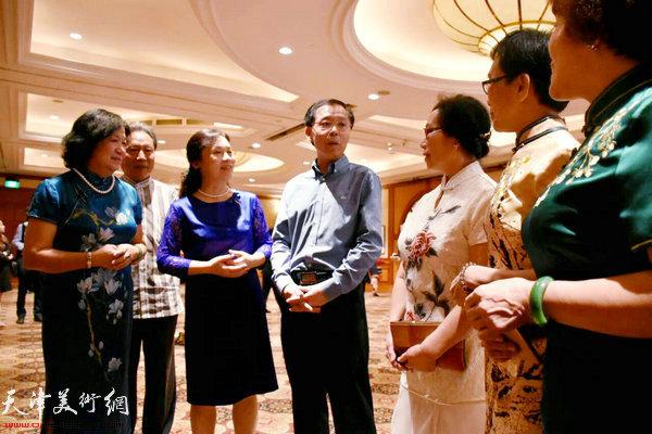 肖江华文化参赞在画展现场与画家交谈。