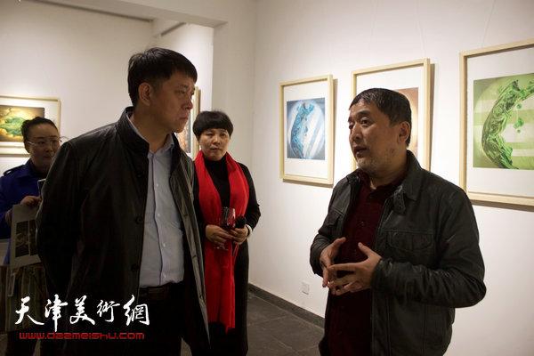 图为范敏与滨海新区区委宣传部副部长王东红在画展现场交谈。