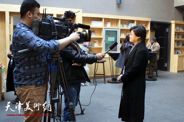 图为滨海新区文广局文艺处处长贺淑荣在画展现场接受媒体采访。