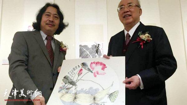 图为贾广健向吴伯雄赠送作品。