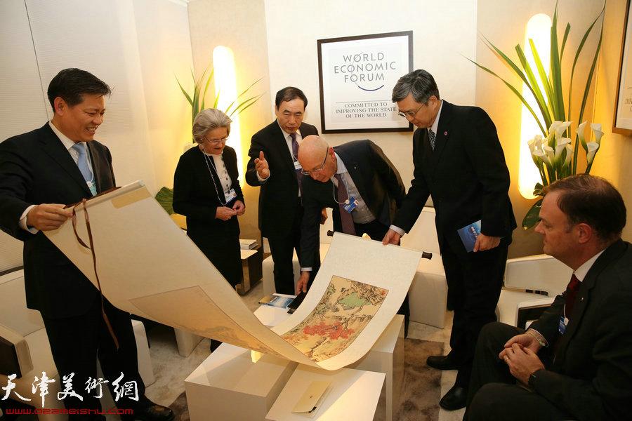 图为赵海山副市长将李旭飞创作的山水作品《秋意》赠送达沃斯论坛主席施瓦布先生